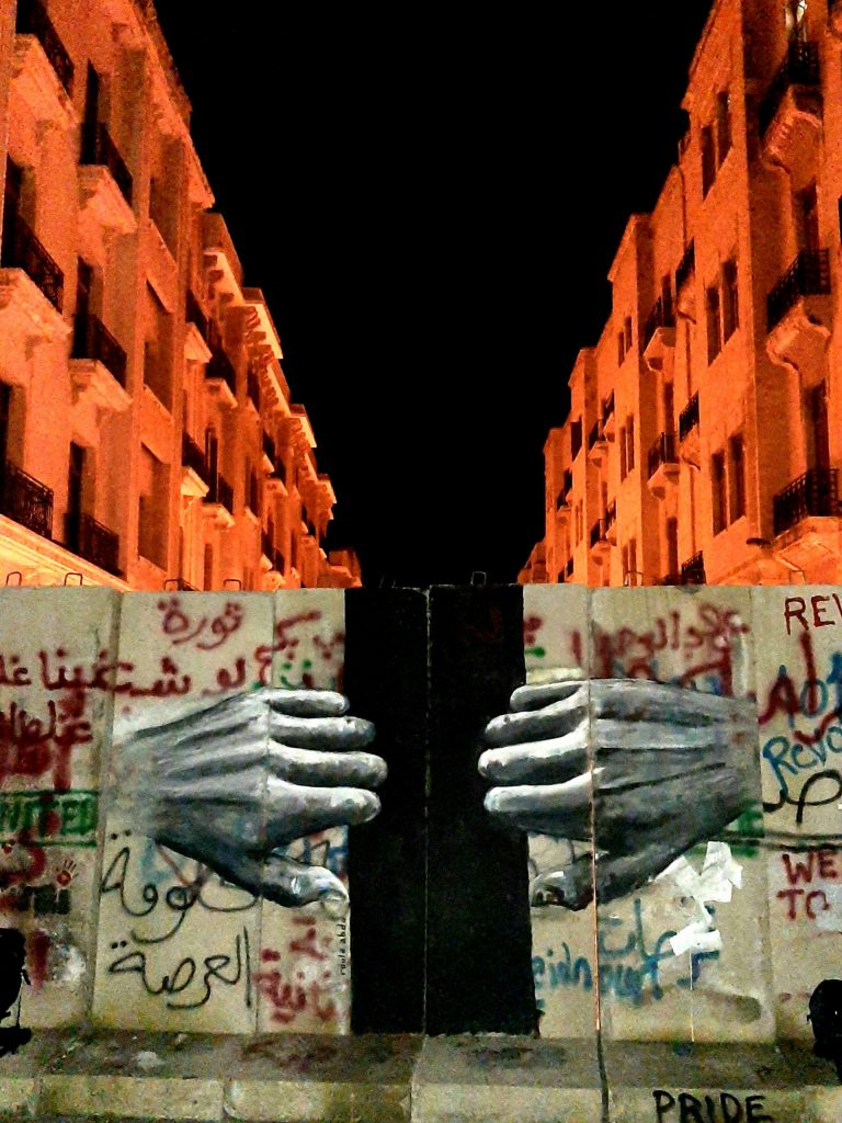 A wall mural in Beirut showing two hands.