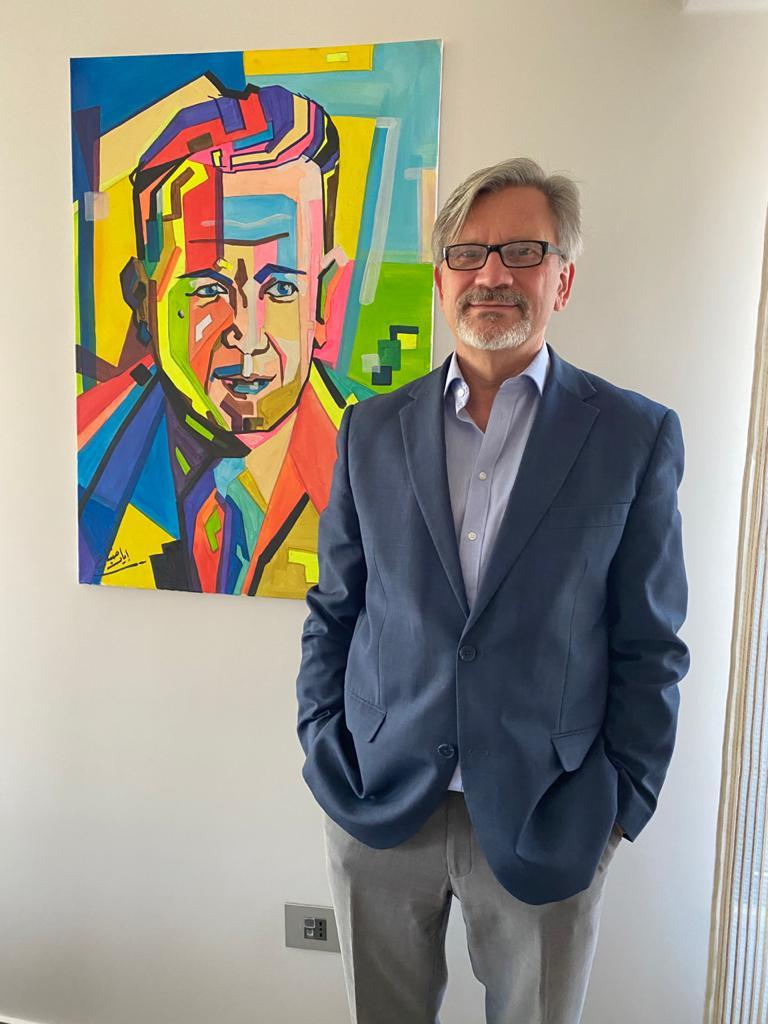 Dominik Bartsch stands next to a portrait of Dag Hammarskjöld by Lyad Fanan, a Syrian artist currently living in the Za'atari refugee camp. Photograph courtesy of Dominik Bartsch.